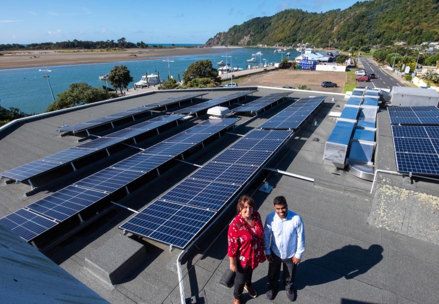 Rachael Burgess and Selva Ganapathy with solar panels at Whakatane office