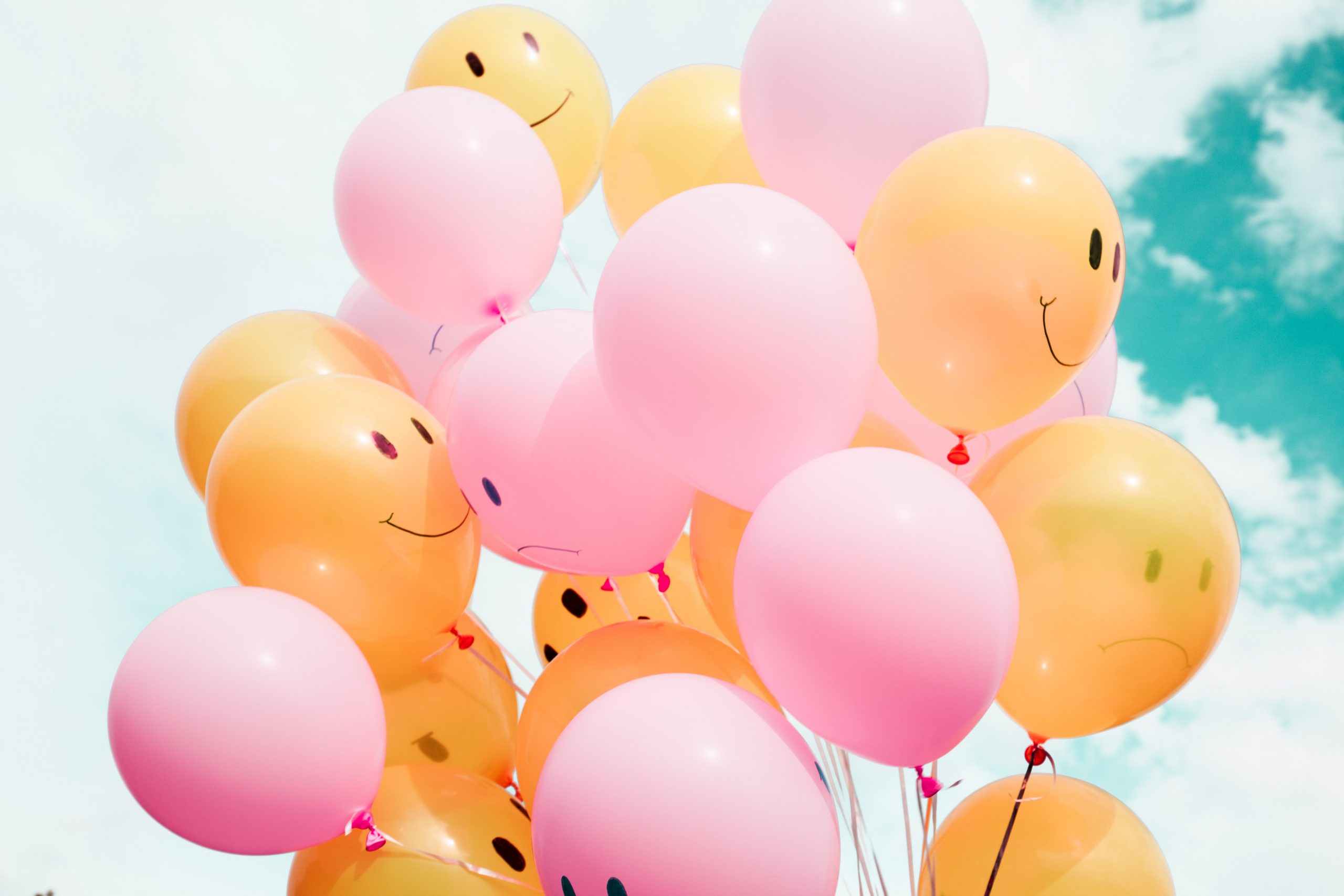 Pink and yellow balloons floating in the sky