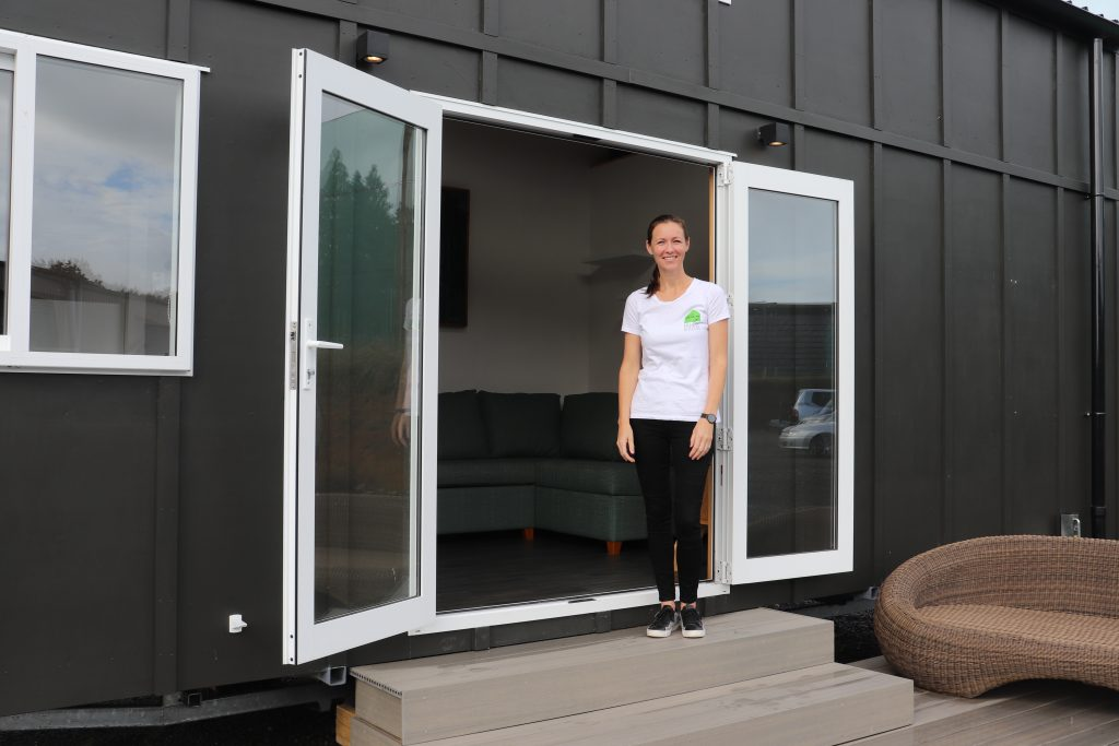 Rebecca Bartlett stands outside a tiny home